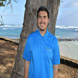 Young man standing on the beach against a tree and smiling.