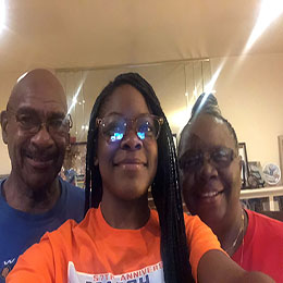 Selfie of an African American couple standing with a smiling African American teenage girl.