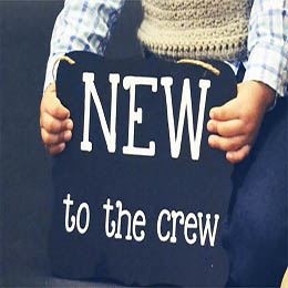 A boy's hands holding a sign that says New to the Crew.