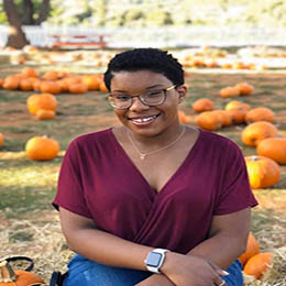 A young African American woman at a pumpkin patch sitting and smiling.