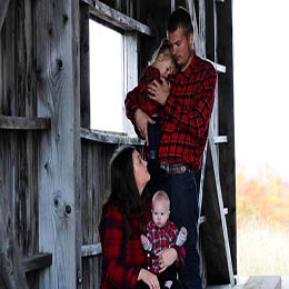 Woman and man holding two kids. All wearing matching plaid shirts in a barn.