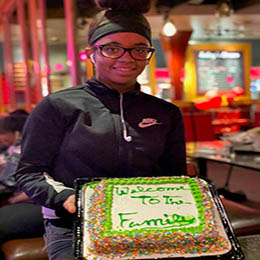 """A young woman smiling and holding a cake that says """"Welcome to the Family."""""""