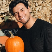 Young man holding a pumpkin and smiling