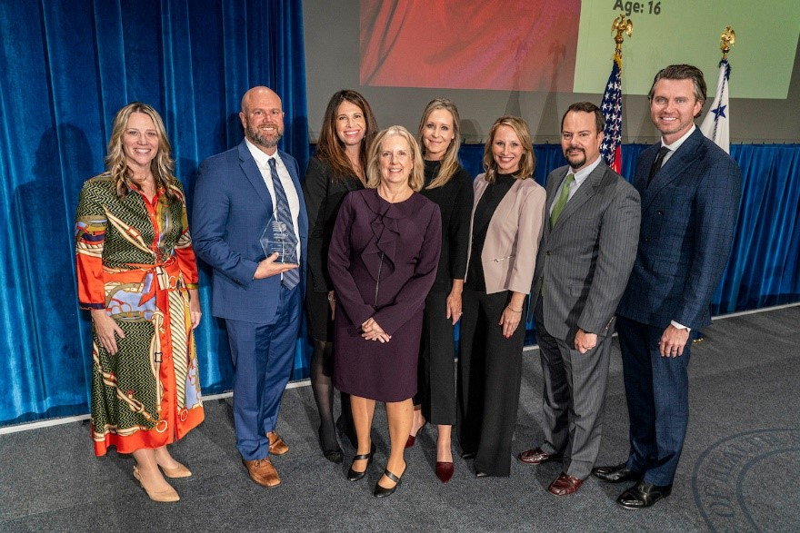 The America's Kids Belong team with Assistant Secretary Lynn Johnson. Left to Right: Janet Kelly, Brian Mavis, Lori Bruegman, Lynn Johnson, Julie Mavis, Kristin Allender, Ryan Kelly, and the AKB Board Chairman Tim Shirk. Photo by Ken Cedeno.