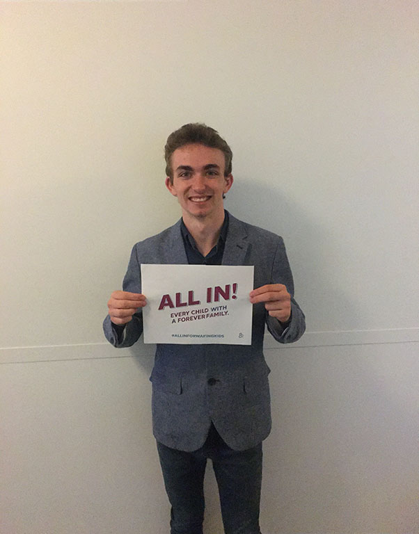 """Joshua Christian, Children's Bureau Youth Engagement Coordinator, holding a sign that says """"Every child with a forever family. ALL IN. #ALLINFORWAITINGKIDS"""""""