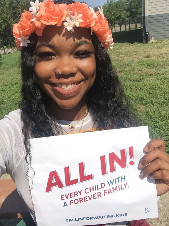 """Dae Rodriguez, youth advocate, holding a sign that says """"Every child with a forever family. ALL IN. #ALLINFORWAITINGKIDS"""""""