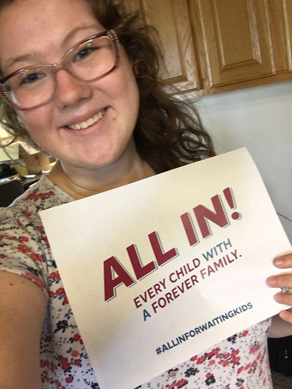 """Shelby Root, youth advocate, holding a sign that says """"Every child with a forever family. ALL IN. #ALLINFORWAITINGKIDS"""""""