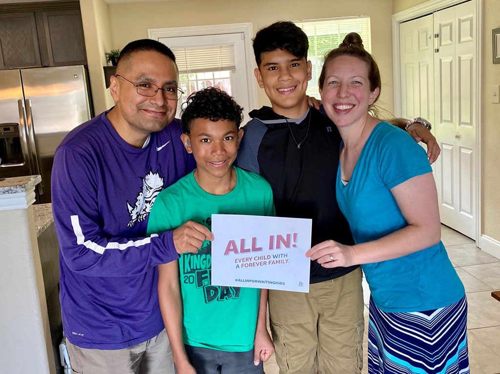 """The Vasquez family holding a sign that says """"Every child with a forever family. ALL IN. #ALLINFORWAITINGKIDS"""""""