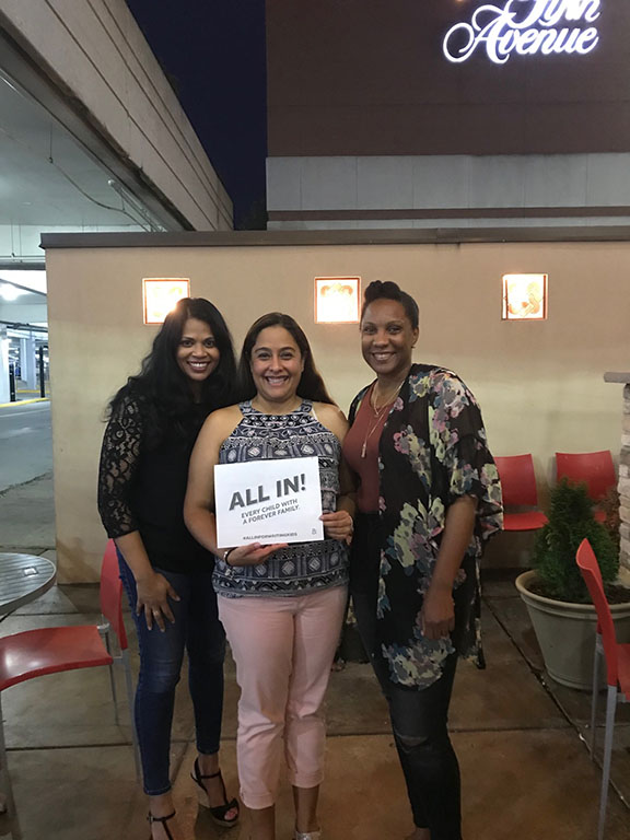 """Community volunteers in Virginia holding a sign that says """"Every child with a forever family. ALL IN. #ALLINFORWAITINGKIDS"""""""