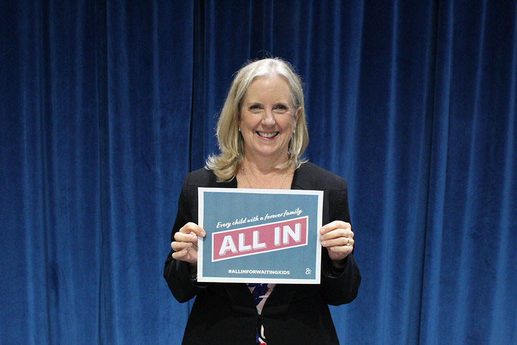 "Assistant Secretary Lynn Johnson holding a sign that reads ""Every child with a forever family. ALL IN. #ALLINFORWAITINGKIDS"""