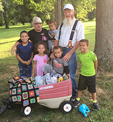 An Elderly Caucasian man and woman with their four foster boys, and one foster girl.