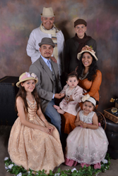 A Hispanic man and woman with their two daughters and three relative foster children. They are sitting and smiling at the camera.