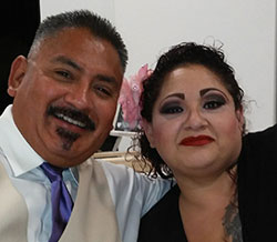 A Hispanic man and women smiling at the camera.