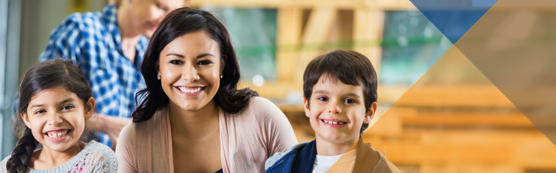 Smiling woman with boy and girl on either side with her hands placed on their upper back.