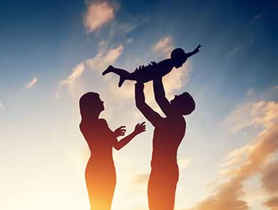 Shadow of mother, father, and child. Father is holding child high above him