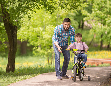 Father pushing son on a bicycle